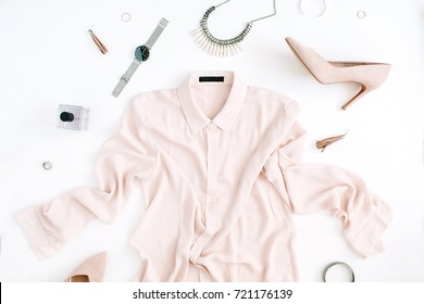 Women modern fashion clothes and accessories. Flat lay female casual style look with pastel blouse, high heels, watch, perfume. Top view.