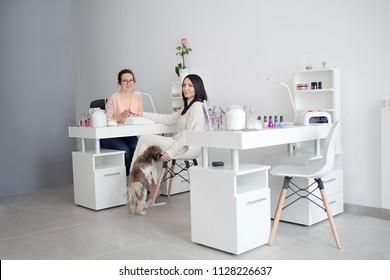 Women at nail salon. Manicure treatment, filing nails