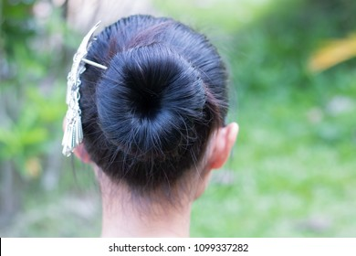 Women nape with hairstyle topknot hair and hairpins with silver in it close-up shallow depth of field on green background