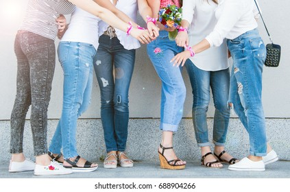Women near the wall in jeans and t-shirts. Women's party before the wedding. Girls with flowers and pink white ribbons on their hands.
