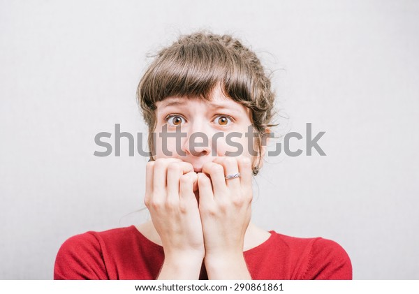 Women nervous nail biting. On a gray background.