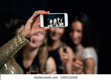 Women night out concept, hen party, celebration. Group of girls drinking champagne, taking selfie in night club.