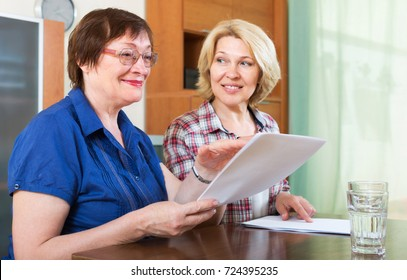 Women notary officer helping mature client drawing up of will