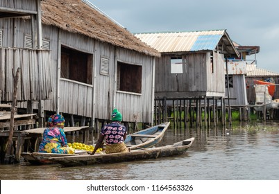 Women on boats going to the market with food. Benin lake Nokoué lifestyle African villager living on house in water. Trading with barter system. West-Africa life in Benin colorful traditional fashion.