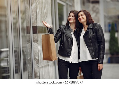 Women on a gray building background. Ladies with shopping bags. Mother with daughter.
