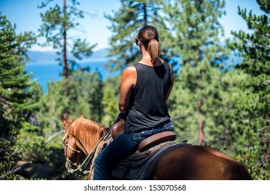 Women on horseback looking out over a lake through the trees