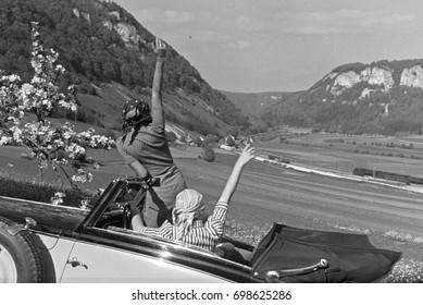 Women on road trip in the country waving hands from car