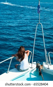 Women on yacht in blue sea seating on stern.
