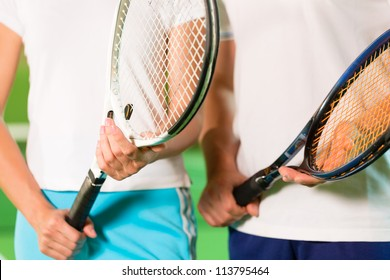 Women, only upper body with racket, playing tennis indoors in court