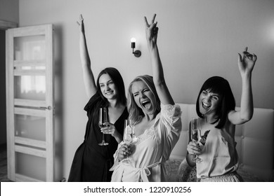 Women party. Beautiful, funny and cheerful girls spending time with pleasure while celebrating hen-party at home, holding a glasses with champagne. Wearing elegant silk pajamas.