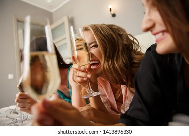 Women party. Cheerful attractive girls clinking glasses of champagne, having fun together, lying on the bed, dressed in silk pajamas. Hen-party at home. Party with alcohol drinks