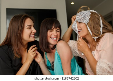 Women party. Cute, joyful girls in pajamas having fun together while celebrating the bridal shower at home. Hen-party concept