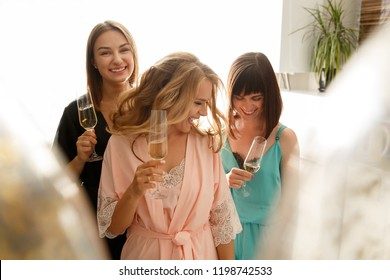 Women party. Girls party. Attractive funny girls in silk robes having fun and drinking a champagne during celebration the bridal shower, at home. Hen-party concept
