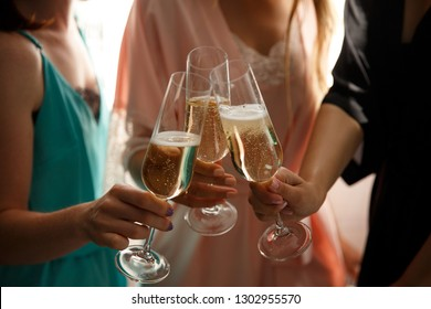 Women party or happy birthday party. Close-up view of sexy, young girls clinking glasses of champagne on hen-party before the wedding day, at home. Dressed in silk nightclothes.
