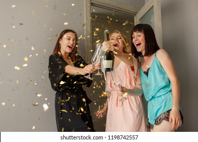 Women party. Incredible, sexy happy girls in silk pajamas drinking a champagne, making toast, on the hen-party. Confetti. At home. Happy birthday party with alcohol drinks