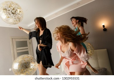 Women party. Three attractive young women having fun while jumping on the bed, with balloons. Dressed up in silk pajamas. At home.