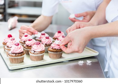 Women in pastry bakery working on muffins putting berries on top