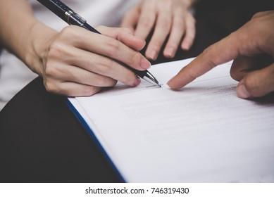 Las mujeres firman un contrato sobre el documento para construir una casa económica con el hombre y la pareja de arquitectos.  Concepto de contrato.