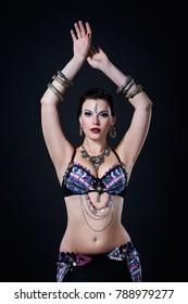 Women performs belly dance in ethnic dress on black background, studio shot