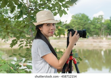 Women photographer with camera and tripod.