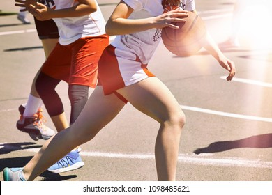 Women play basketball. Group of happy teenage girls in sports uniform, playing basketball outdoors in the city.