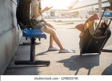 Women play phone while waiting for the bus to travel.