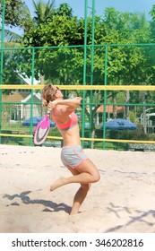 Women player plays beach tennis.