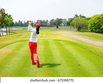 Women playing golf on summer with hitting shot on green grass