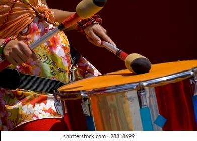 Women playing the orange drum.