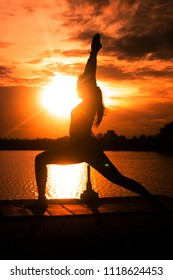 Women are playing yoga at Reservoir area with Sunset