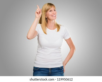 Women Pointing Up With Hand On Hip against a grey background
