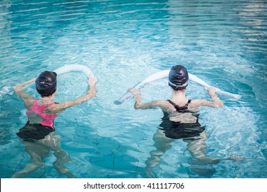 Women in the pool with foam rollers at the leisure center