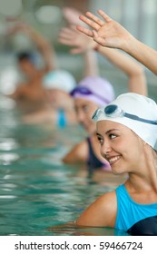 Women in a pool practicing synchronized swimming and smiling