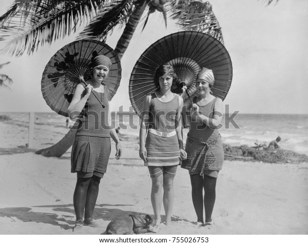 Women pose in bathing suits at an American east coast beach between 1910-1920. The younger woman in the center has bare legs, but the others wear stockings.