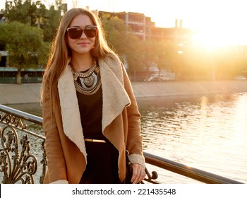 Women posing near water in sunglasses at sunset backlit