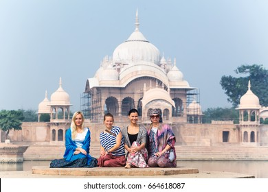 Women posing sitting near Kusum Sarovar Govardhan Mandir . India, Govardhan, November 2016
