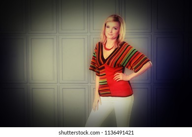 Women posing in studio. She is dressed in a striped knitted blouse and white jeans. She has a necklace on her neck. Clothing in the style of the 1970s. One hand at the waist. Unusual background.