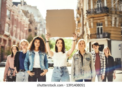 Women power. Young woman is holding blank signboard over her head while standing on the road around female activists.