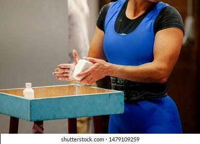 women powerlifter apply gym chalk on hands before attempting in deadlift