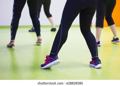 Women practice dancing in a gym. Sports exercises