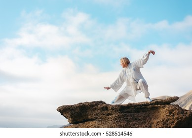 Women practicing Taijiquan in beautiful nature. Exercise in morning day on the sea coast
