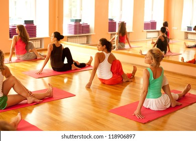 Women practicing yoga at health club