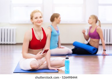Women practicing yoga at health club. Young girls talking and relaxing after fitness, Yoga instructor speaks on the phone after training, lifestyle concept.