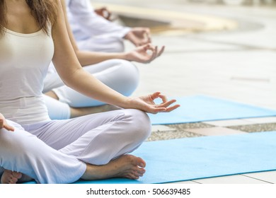 Women practicing yoga and meditating by the pool.  Relax and healthiness concept