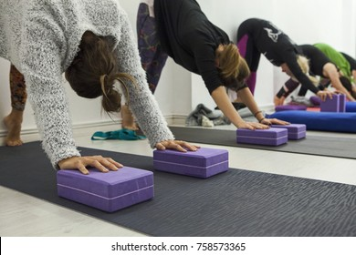 Women practicing yoga therapy, stretching in down dog using blocks and the wall, downward facing dog, exercise for spine and shoulders flexibility, working out, closeup