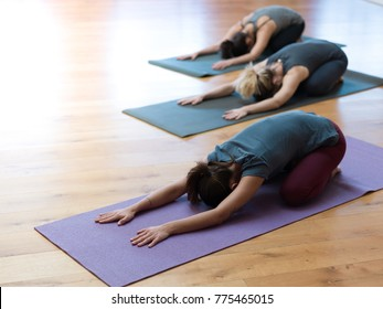 Women practicing yoga together and performing the child's pose on a mat, healthy lifestyle and spirituality concept