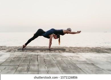 women practising acro yoga asana near sea on sunrise