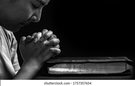Women praying to God and spending time in God's word with the bible on black