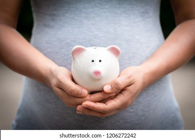 Women is pregnant hold a pig bank in the public park, a saving money for future investment concept.