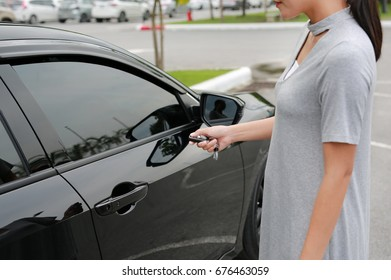Women pressing the button on the remote to lock or unlock the car